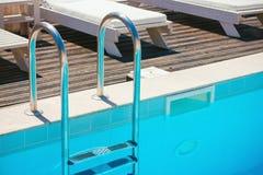 有空的游泳池的镀铬物台阶 免版税库存照片