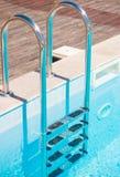 有空的游泳池的镀铬物台阶 库存图片