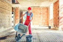 有空的独轮车的工作者在建造场所 库存照片