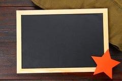 有空的空间、军用盖帽和红色星的黑板在一张木桌上 祖国和5月9的防御者的天 免版税库存图片