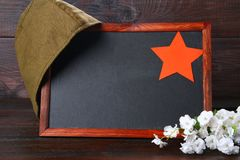 有空的空间、军用盖帽和红色星的黑板在木头 免版税库存图片