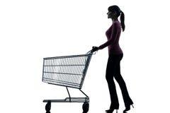 有空的购物车剪影的妇女 免版税图库摄影