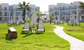 有空的sunbeds的棕榈滩反对油罐旅馆& Suitel 设置在田园诗海滩前的locati 免版税库存图片