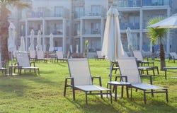 有空的sunbeds的棕榈滩反对油罐旅馆& Suitel 设置在田园诗海滩前的locati 免版税库存照片