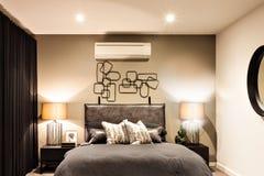 有空调器的现代卧室在豪华房子里 免版税库存图片