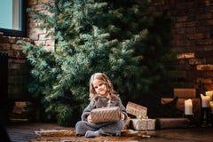 有穿一件温暖的毛线衣的白肤金发的卷发的愉快的女孩拿着礼物盒,当坐地板在旁边时 图库摄影