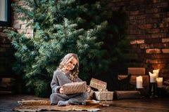 有穿一件温暖的毛线衣的白肤金发的卷发的愉快的女孩拿着礼物盒,当坐地板在旁边时 免版税图库摄影