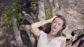 有穿一件长的白色夏天时尚礼服的长的深色的头发的画象迷人的少女说谎在一棵干树 股票录像