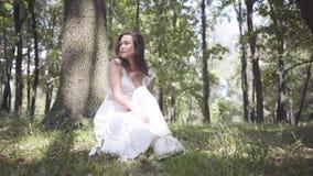 有穿一件长的白色夏天时尚礼服的长的深色的头发的画象逗人喜爱的少女坐在的一棵树下 股票录像