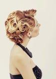 有穿少许黑礼服的金发的美丽的妇女接触她的从后面的脖子意图在白色 免版税库存图片