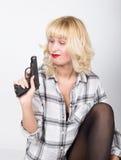 有穿格子花呢上衣的红色嘴唇的特写镜头画象美丽的白肤金发的女孩,拿着枪和失望看 免版税库存照片