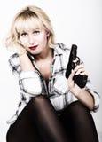 有穿格子花呢上衣的红色嘴唇的特写镜头画象美丽的白肤金发的女孩,拿着枪 免版税库存照片