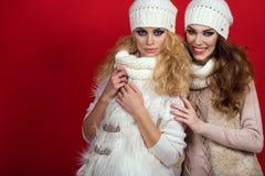 有穿白色羊毛帽子、围巾、毛线衣和背心在红色背景的完善的微笑的两个华美的女朋友 免版税库存照片