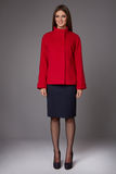 有穿着一条黑暗的裙子的晚上构成的美丽的性感的年轻女商人对膝盖羊毛红色外套夹克高起动高hee 图库摄影