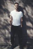 有穿空白的白色T恤杉和黑牛仔裤的纹身花刺的有胡子的人 砖墙背景 垂直的大模型,软 免版税库存照片