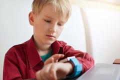 有穿红色时髦的衬衣的金发的一个逗人喜爱的男孩坐白色长沙发与看他聪明的手表tou的膝上型计算机一起使用 免版税图库摄影