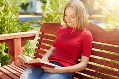 有穿红色毛线衣和牛仔裤的公平的头发的宁静的妇女坐在拿着书读书高兴地的木大长凳 学生 图库摄影