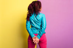 有穿蓝色皮夹克和洋红色牛仔裤的紫色头发的美丽的少妇 常设姿势,隔绝在色的backgroun 免版税库存照片