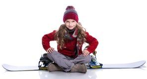 有穿被编织的毛线衣,围巾,帽子的卷曲发型的微笑的小女孩坐蓝色雪板,隔绝在白色 免版税库存图片