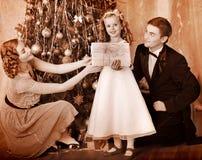 有穿戴圣诞树的子项的家庭。 库存图片