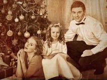 有穿戴圣诞树的子项的家庭 免版税库存图片