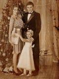 有穿戴圣诞树的子项的家庭 免版税库存照片