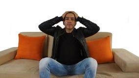 有穿黑T恤杉和黑皮夹克的被会集的头发完成的弓的年轻西班牙人坐沙发 免版税图库摄影