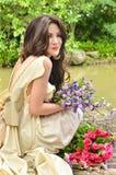 有突出在庭院里的花花束的美丽的妇女 库存图片