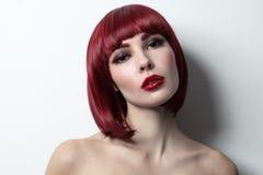 有突然移动理发的年轻美丽的红发女孩和 库存图片