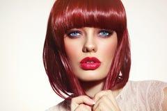 有突然移动理发的美丽时尚红头发人女孩和时髦做 免版税库存图片