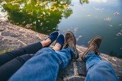有窃笑和人的一名妇女有休息在湖旁边的起动的 免版税库存照片