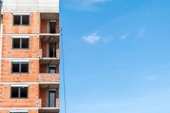 有窗口和明白蓝天的新的居民住房建造场所与拷贝空间,工业建筑学概念 库存照片