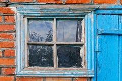 有窗口和蓝色门的砖墙 库存照片