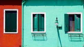 有窗口房子的红色和绿色墙壁 免版税库存照片