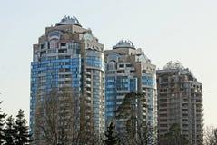 有窗口的三个高天空背景的房子和阳台 免版税库存图片