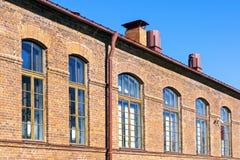有窗口的减速火箭的红砖房子墙壁 免版税库存照片