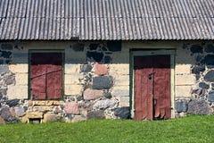 有窗口的墙壁和老石房子的门 免版税库存照片