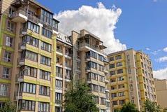 有窗口的多层的有植被分支的房子和阳台反对天空的 库存照片