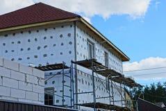 有窗口的白色私有未完成的房子在篱芭后 免版税库存图片
