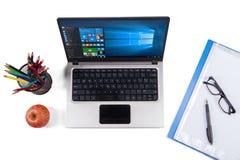 有窗口10和文具的笔记本计算机 免版税库存图片