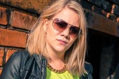 有站立反对砖的金发的年轻确信的妇女 免版税库存图片