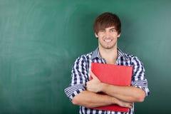 有站立反对黑板的红色黏合剂的男学生 免版税库存图片