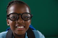 有站立反对绿色背景的眼镜的微笑的女小学生 免版税库存图片