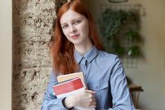 有站立和拿着书的长的红色头发的微笑的逗人喜爱的害羞的少妇 免版税库存照片