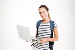 有站立和拿着膝上型计算机的背包的愉快的逗人喜爱的学生女孩 库存图片