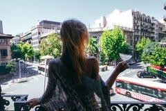 有站立在一个阳台的玻璃的一个女孩在巴塞罗那 免版税库存图片