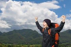 有站立在一座山顶部的背包的年轻人用他的手 免版税库存照片