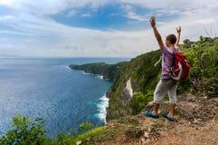 有站立在一座山顶部的背包的远足者用被举的手 免版税库存图片