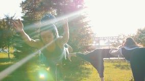 有站立在一条腿的蓝色dreadlocks的一年轻女人和保持平衡-瑜伽外部 股票视频
