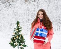 有站立在一棵圣诞树附近的礼物盒的青少年的女孩在冬天森林里 免版税库存图片